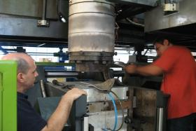 Removing the extrusion die from the blow molding machine.